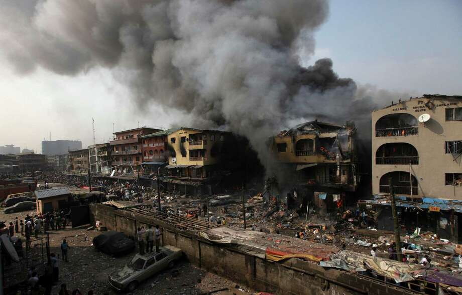 Residents look  as  a fire burns out a residential homes and a warehouse on Lagos Island in Lagos, Nigeria, on Wednesday. An explosion ripped through a warehouse Wednesday where witnesses say fireworks were stored in Nigeria's largest city, sparking a fire. It wasn't immediately clear if anyone was injured in the blast that firefighters and locals struggled to contain. Photo: AP