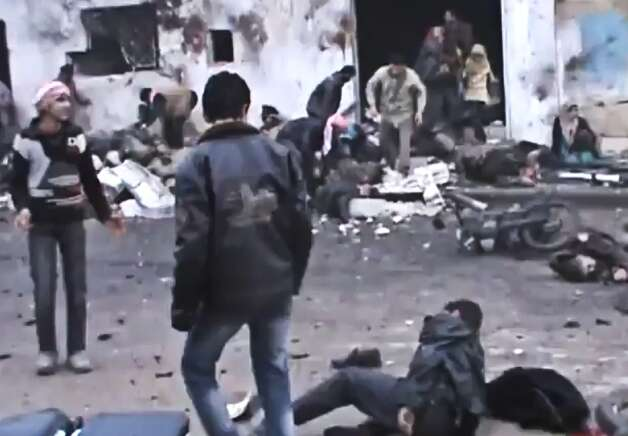 This Sunday, Dec. 23, image taken from video obtained from the Shaam News Network, which has been authenticated based on its contents and other AP reporting, shows Syrians removing the bodies of those killed after a government airstrike hit the Hama Suburb of Halfaya, Syria. A government airstrike Sunday on a bakery in a rebel-held town in central Syria killed tens of people, which left scattere