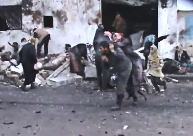 This Sunday, Dec. 23, image taken from video obtained from the Shaam News Network, which has been authenticated based on its contents and other AP reporting, shows a Syrian man carrying an elderly woman after a government airstrike hit the Hama Suburb of Halfaya, Syria. A government airstrike Sunday on a bakery in a rebel-held town in central Syria killed tens of people, which left scattered bodies and debris up and down a s