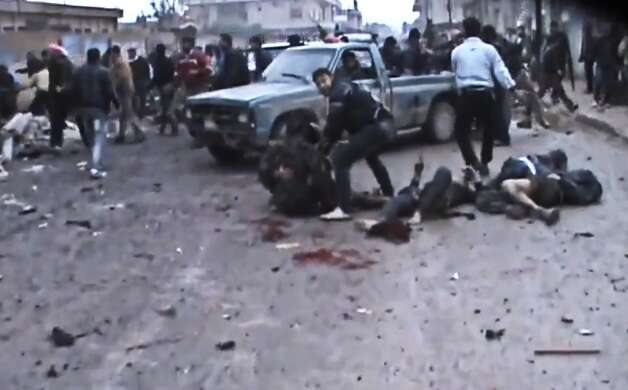 This Sunday, Dec. 23, 2012 image taken from video obtained from the Shaam News Network, which has been authenticated based on its contents and other AP reporting, shows Syrians removing the bodies of those killed after a government airstrike hit the Hama Suburb of Halfaya, Syria. A government airstrike Sunday on a bakery in a rebel-held town in central Syria killed tens of people, which left scattered bodies and debris up and down a street, and more than a dozen wounded were trapped in tangled heap of dirt and rubble, activists said. Photo: AP