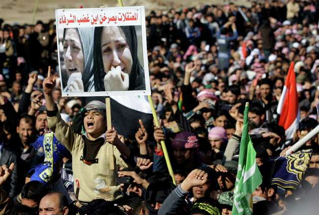 "Protesters chant slogans against Iraq's Shiite-led government as they wave national flags during a demonstration in Fallujah, 40 miles west of Baghdad, Iraq, on Friday. Thousands of Iraqi Sunnis massed along a major western highway and in other parts of the country Friday for what appear to be the largest protests yet in a week of demonstrations, intensifying pressure on the Shiite-led government. The placard in Arabic reads, ""women prisoners scream: where is the honorable people's anger?"" Photo: AP"