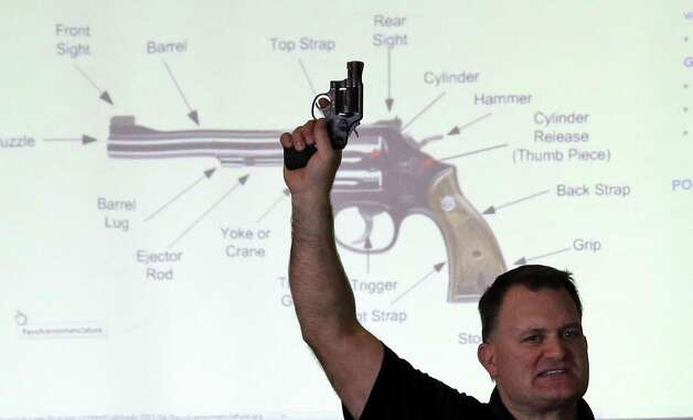 Clark Aposhian, President of Utah Shooting Sport Council, holds a pistol during concealed weapons training for 200 Utah teachers on Thursday in West Valley City, Utah. The Utah Shooting Sports Council offered six hours of training in handling concealed weapons in the latest effort to arm teachers to confront school assailants. Photo: AP