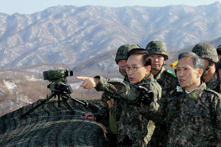 South Korean President Lee Myung-bak, wearing glasses, talks with Defense Minister Kim Kwan-jin, right, and a division commander Cho Gook-je, left, as they look towards North Korea during his visit to a guard post near the demilitarized zone (DMZ) that separates the two Koreas since the Korean War, in Hwacheon, South Korea, Thursday. Photo: AP