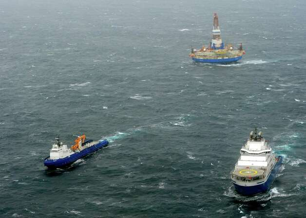 In this photo provided by the United States Coast Guard, the tugs Aiviq and Nanuq tow the mobile drilling unit Kulluk while a Coast Guard helicopter from Air Station Kodiak transports crew members on Saturday 80 miles southwest of Kodiak City, Alaska. The tug lost the initial tow Thursday and suffered several engine failures prompting the deployment of response assets by the Coast Guard and Royal Dutch Shell. Photo: AP