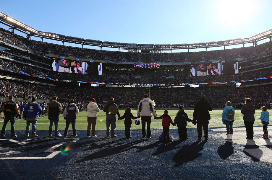 EAST RUTHERFORD, NJ - DECEMBER 30: Families from Sandy Hook Elementary School in Newtown, Connecticut surround the field during the national anthem before the game between the New York Giants and the Philadelphia Eagles at MetLife Stadium on December 30, 2012 in East Rutherford, New Jersey. (Photo by Elsa/Getty Images)