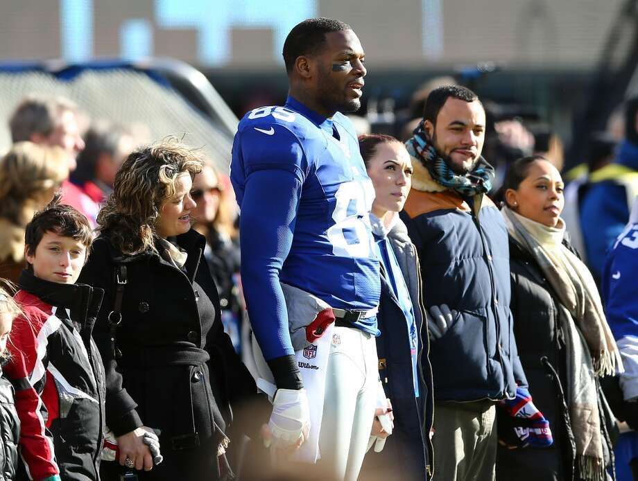 EAST RUTHERFORD, NJ - DECEMBER 30: Martellus Bennett #85 of the New York Giants holds hands with families from Sandy Hook Elementary School in Newtown, Connecticut during the national anthem before the game New York Giants and the Philadelphia Eagles at MetLife Stadium on December 30, 2012 in East Rutherford, New Jersey. (Photo by Elsa/Getty Images)