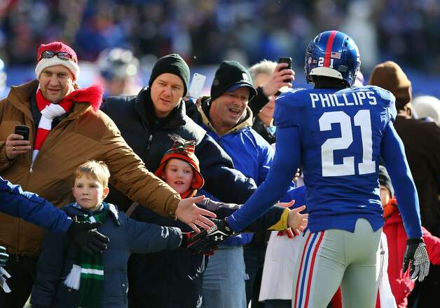 EAST RUTHERFORD, NJ - DECEMBER 30: Kenny Phillips #21 of the New York Giants greets families from Sandy Hook Elementary School in Newtown, Connecticut before the game between the New York Giants and the Philadelphia Eagles at MetLife Stadium on December 30, 2012 in East Rutherford, New Jersey. (Photo by Elsa/Getty Images)