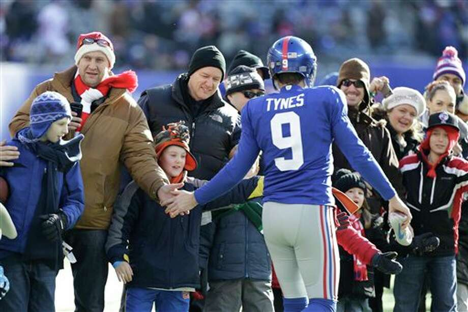 New York Giants kicker Lawrence Tynes (9) greets a contingent of teachers, parents, and students from Sandy Hook Elementary School in Newtown, Conn. before an NFL football game Sunday, Dec. 30, 2012 in East Rutherford, N.J. (AP Photo/Kathy Willens)