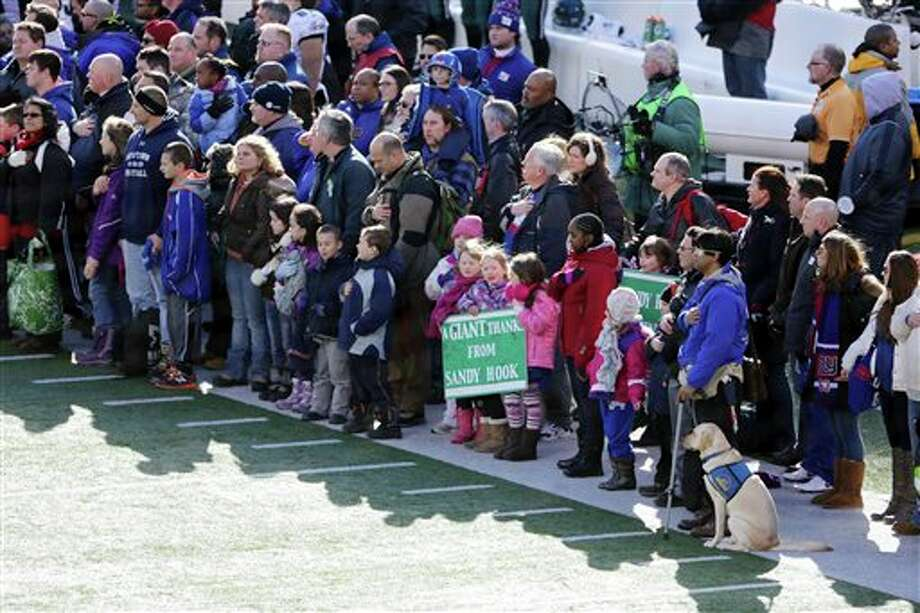 A contingent of teachers, parents, and students from Sandy HookElementary School in Newtown, Conn., take part in pre-game ceremonies before Sunday's game between the New York Giants and the Philadelphia Eagles at MetLife Stadium Sunday, Dec. 30, 2012 in East Rutherford, N.Y. (AP Photo/Peter Morgan)