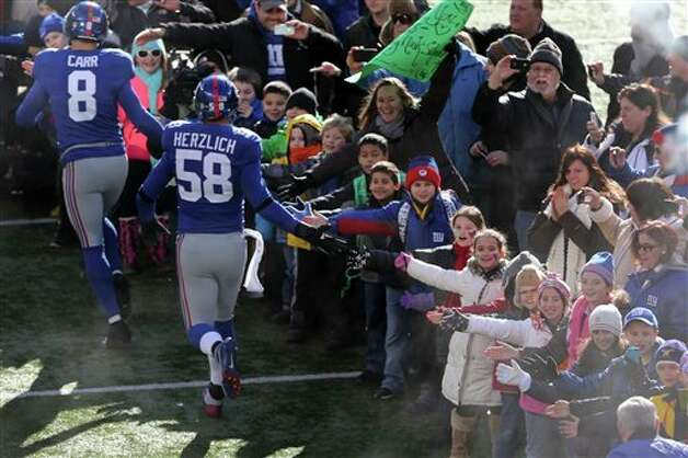 New York Giants quarterback David Carr (8) and Mark Herzlich (58) greet fans before an NFL football game Sunday, Dec. 30, 2012 in East Rutherford, N.Y. A contingent of teachers, parents, and students from Sandy Hook Elementary School in Newtown, Conn., will be honored before Sunday's game between the New York Giants and the Philadelphia Eagles at MetLife Stadium. (AP Photo/Peter Morgan)