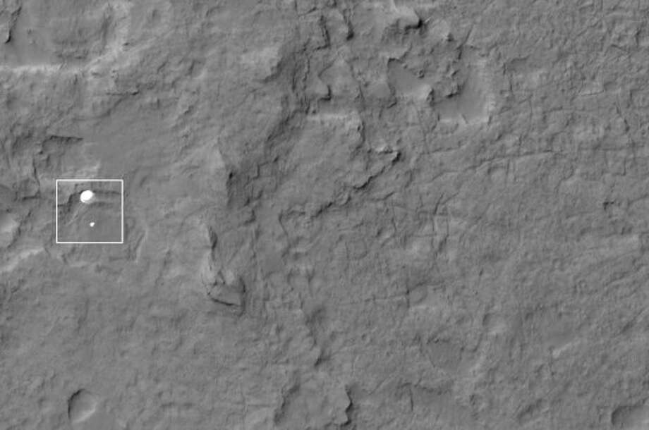 In this handout image provided by NASA, Curiosity and its parachute are seen by NASA's Mars Reconnaissance Orbiter as Curiosity descends to the surface of Mars on August 5. (NASA / Getty Images)