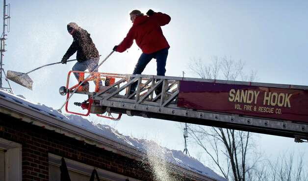 Guy Veneruso, left, and Greg Gnandt shovel snow from the roof of the Sandy Hook fire station Sunday, Dec. 30, 2012, in Newtown, Conn. Gnadt said they are preparing the roof of the firehouse to install 26 copper stars in memory of the victims of the Sandy Hook school shooting. They plan to begin the installation on New Year's Day. Photo: Brett Coomer, Brett Coomer/Hearst Newspapers / The News-Times