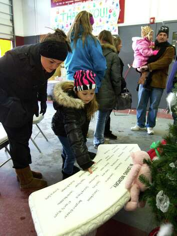 Kalie Braziel, left, and Taya Lindsey, 7, of Magnolia, Texas, look at a memorial bench dedicated to the victims of the Sandy Hook school shooting Sunday, Dec. 30, 2012, at the Sandy Hook fire station in Newtown, Conn. ( Brett Coomer / Hearst Newspapers ) Photo: Brett Coomer, Brett Coomer/Hearst Newspapers / The News-Times