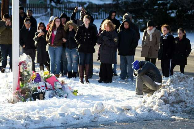 A gathering of people surround the corner of Dickinson Drive and Riverside Road as they mourn the victims of the Sandy Hook school shooting Sunday, Dec. 30, 2012, in Newtown, Conn. Even though the large memorial was removed from the site, people continue to stop and leave tributes. Photo: Brett Coomer, Brett Coomer/Hearst Newspapers / The News-Times