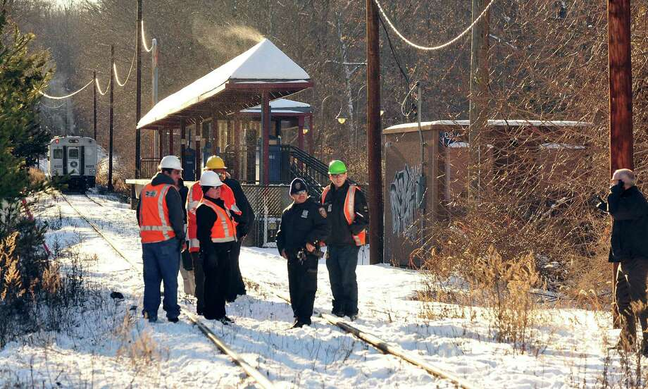 Transit workers and Redding Police occupy the scene where a car was hit by a train near the intersection of Simpaug Turnpike and Long Ridge Road in West Redding Center, Conn., Sunday, Dec. 30, 2012. The West Redding Train Station stands in the background. Photo: Michael Duffy
