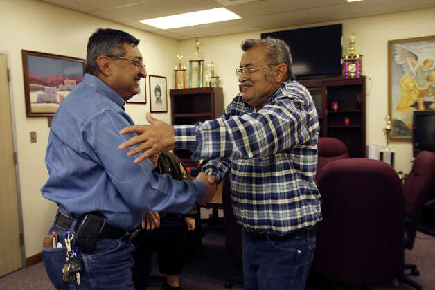 Gonzalez (left) greets Zapata Community Center Manager Rolando Villarreal at Gonzalez's retirement tamalada. Photo: Jerry Lara, San Antonio Express-News / © 2012 San Antonio Express-News
