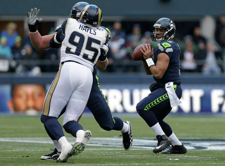 St. Louis Rams' William Hayes (95) pressures as Seattle Seahawks quarterback Russell Wilson, right, looks to pass in the first half of an NFL football game on Sunday in Seattle. Photo: AP Photo/Elaine Thompson