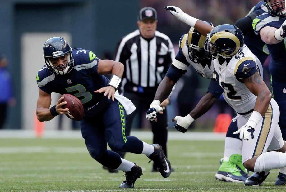 Seattle Seahawks quarterback Russell Wilson (3) scrambles away from St. Louis Rams' Eugene Sims, right, and William Hayes, second from right, in the first half of an NFL football game against the St. Louis Rams on Sunday in Seattle. Photo: AP Photo/Elaine Thompson