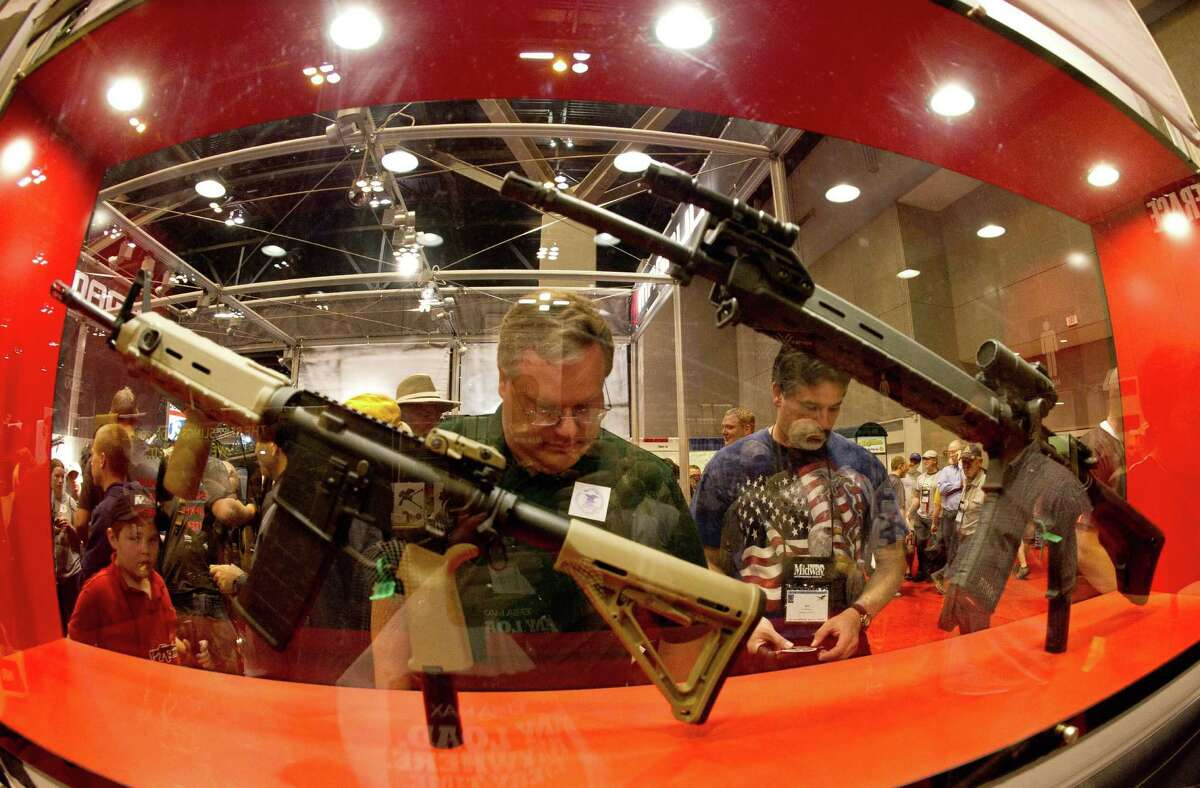 Gun enthusiasts examine firearms at the National Rifle Association's annual meeting in St. Louis in April. NRA defenders say corporate donations from firearms companies to the organization are the norm for advocacy organizations and industry players.