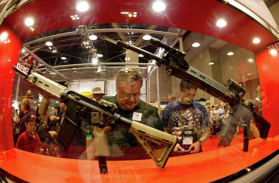 People look over firearms on the floor of an NRA exhibit in St. Louis in April. Since the Newtown, Conn., school massacre a month ago, gun sales have skyrocketed.  Photo: Karen Bleier, Getty Images / AFP ImageForum