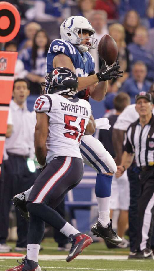 Indianapolis Colts' Coby Fleener (80) tries to make a catch while being defended by Houston Texans' Darryl Sharpton (51) during the first half of an NFL football game Sunday, Dec. 30, 2012, in Indianapolis. The pass was incomplete. (AP Photo/AJ Mast) Photo: AJ Mast, Associated Press / FR123854 AP