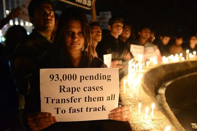 Indian protesters hold candles and posters  during a rally in Ahmedabad on December 30, 2012, following following the cremation of a gangrape victim in the Indian capital. The victim of a gang-rape and murder which triggered an outpouring of grief and anger across India was cremated at a private ceremony, hours after her body was flown home from Singapore. A student of 23-year-old, the focus of nationwide protests since she was brutally attacked on a bus in New Delhi two weeks ago, was cremated away from the public glare at the request of her traumatised parents. AFP PHOTO / Sam PANTHAKYSAM PANTHAKY/AFP/Getty Images Photo: Sam Panthaky, AFP/Getty Images