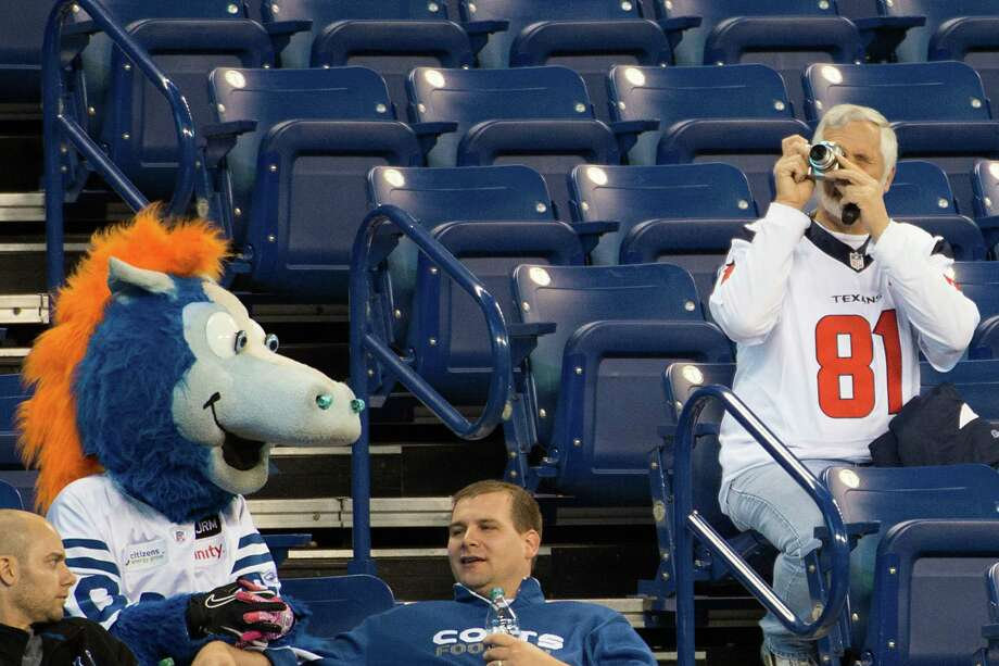 A Texans fan takes photos of the stadium as the Colts mascot sits nearby. Photo: Smiley N. Pool, Houston Chronicle / © 2012  Houston Chronicle