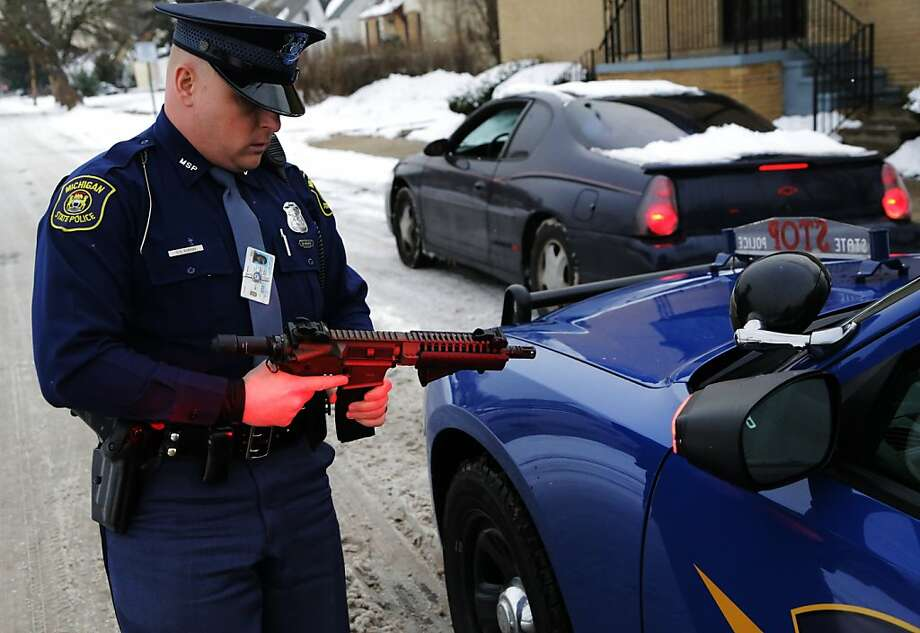 Michigan State Police Trooper Chris Kurish checks a gun being carried by the driver of a car after a traffic stop on Detroit's west side on Friday, Dec. 28, 2012. Michigan has 16 percent fewer police officers on the street now than it did a decade ago, and communities around the state are trying to find more efficient ways to keep people safe. (AP Photo/Detroit Free Press, Ryan Garza) Photo: Ryan Garza, Associated Press