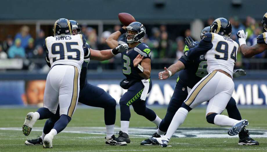 Seattle Seahawks quarterback Russell Wilson passes under pressure from St. Louis Rams' William Hayes (95) and St. Louis Rams' Robert Quinn (94) in the first half of an NFL football game on Sunday in Seattle. Photo: AP Photo/Elaine Thompson