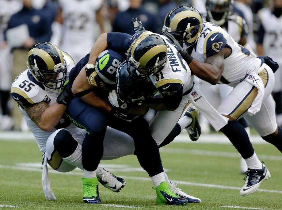 Seattle Seahawks' Zach Miller is tackled by St. Louis Ram' James Laurinaitis (55), Cortland Finnegan (31) and Quintin Mikell (27) during the first half of an NFL football game on Sunday in Seattle. Photo: AP Photo/Elaine Thompson