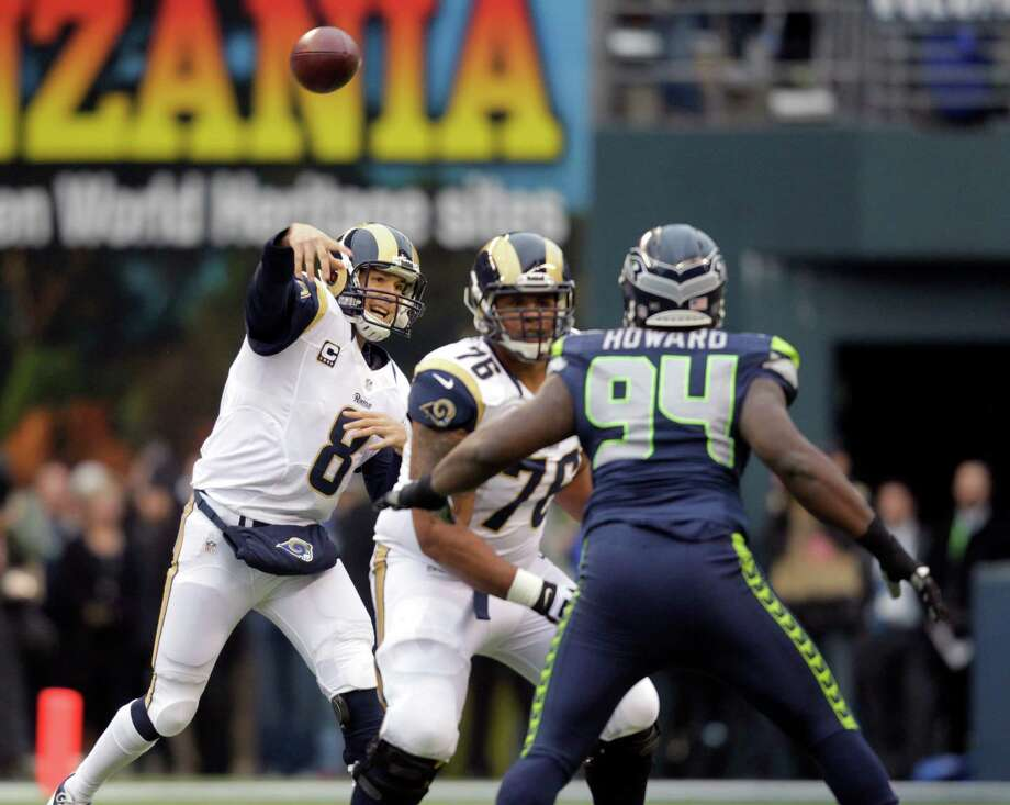 St. Louis Rams quarterback Sam Bradford passes the ball under pressure from Seattle Seahawks defensive tackle Jaye Howard in the first half of an NFL football game, Sunday in Seattle. Photo: AP Photo/Elaine Thompson