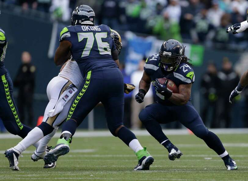 Seattle Seahawks' Marshawn Lynch (24) rushes as Russell Okung (76) blocks in the first half of an NF