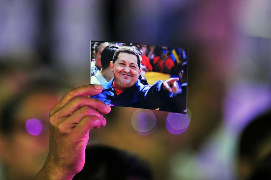 "A woman holds a  picture of Venezuelan President Hugo Chavez during the concert ""Song, Life and Hope, celebrated in his honor, December 17, 2012 in Managua.  Chavez is recovering in Cuba following a fourth operation for a recurrence of cancer.   AFP PHOTO/Hector RETAMALHECTOR RETAMAL/AFP/Getty Images Photo: Hector Retamal, AFP/Getty Images"