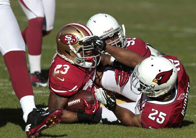 49ers Running back LaMichael James (23) is brought down by Arizona Cardinals safety Kerry Rhodes (25) and defensive end Calais Campbell (93) during the first half of the San Francisco 49ers game against the Arizona Cardinals at Candlestick Park in San Francisco, Calif., on Sunday December 30, 2012. Photo: John Storey, Special To The Chronicle