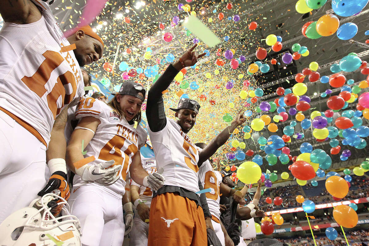 Texas players D.J. Grant (18), Matthew Zapata (40) and Jeremy Hills (05) join other players on the podium to celebrate their victory over Oregon State in the Valero Alamo Bowl on Saturday, Dec. 29, 2012. Texas won, 31-27.