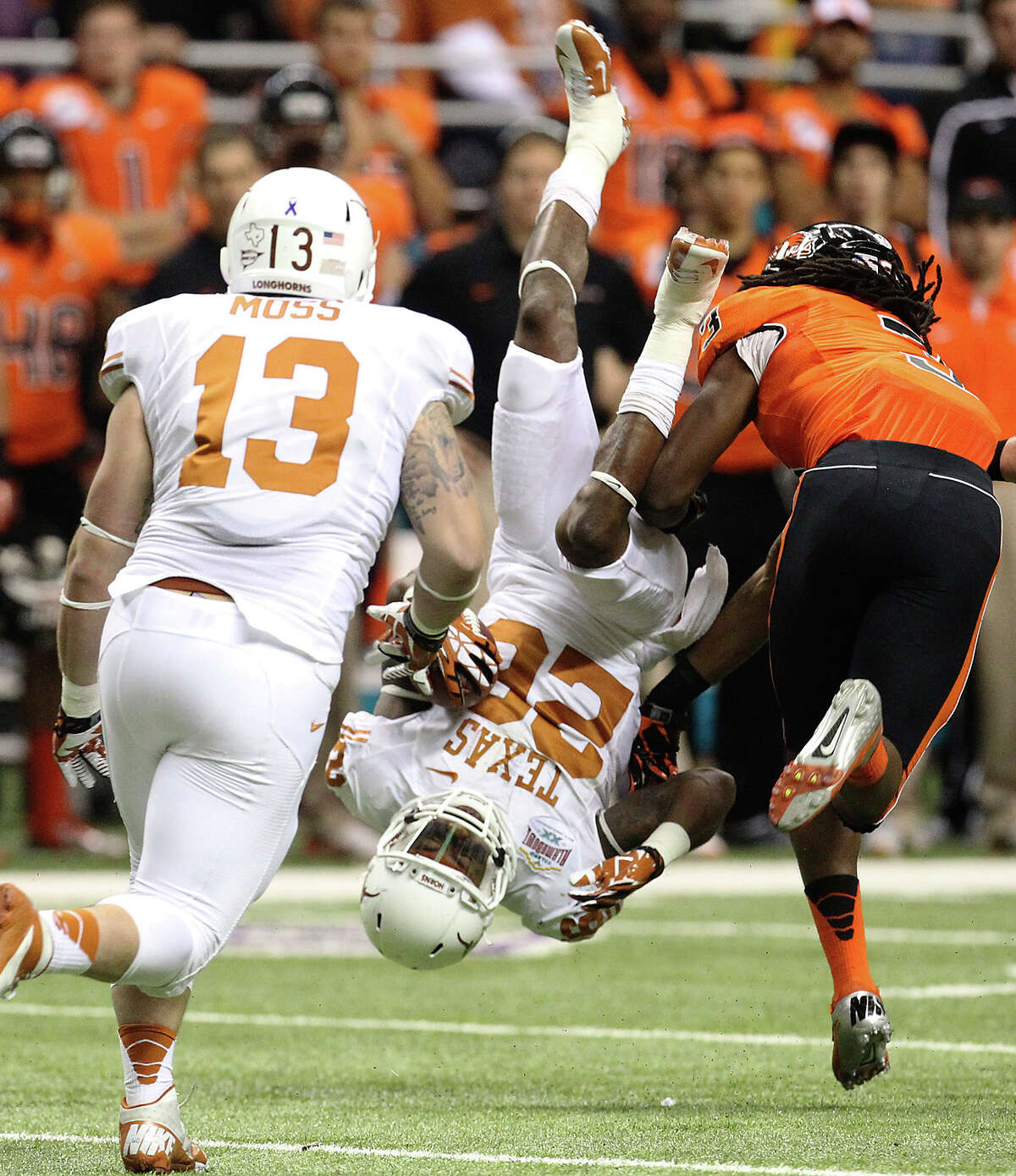 Texas' D. J. Monroe (26) gets flipped over while returning a kick against Oregon State's Anthony Watkins (03) in the first half of the Valero Alamo Bowl on Saturday, Dec. 29, 2012.