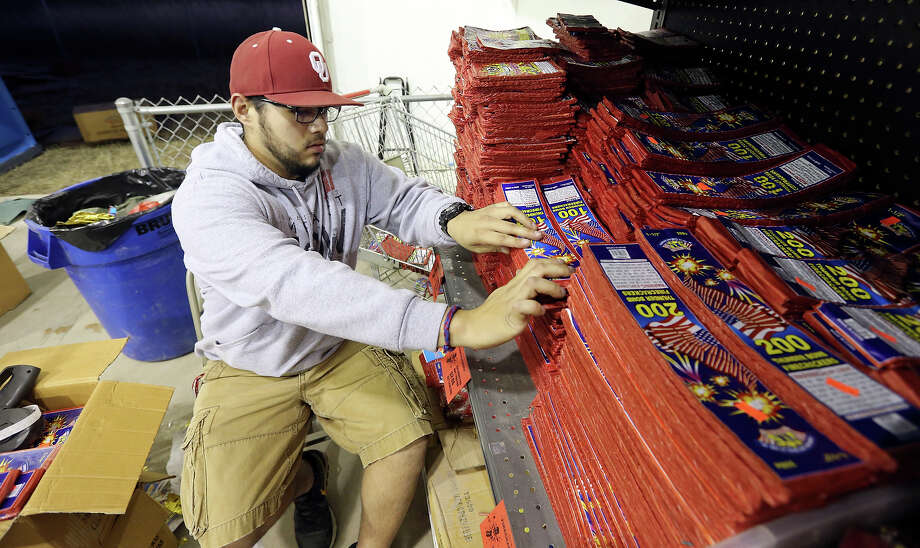Angelo Rizo stocks the shelves Saturday Dec. 21, 2013 at the Mr. W Fireworks Warehouse at the intersection of IH-37 South and Loop 1604. Photo: Edward A. Ornelas, San Antonio Express-News / © 2013 San Antonio Express-News