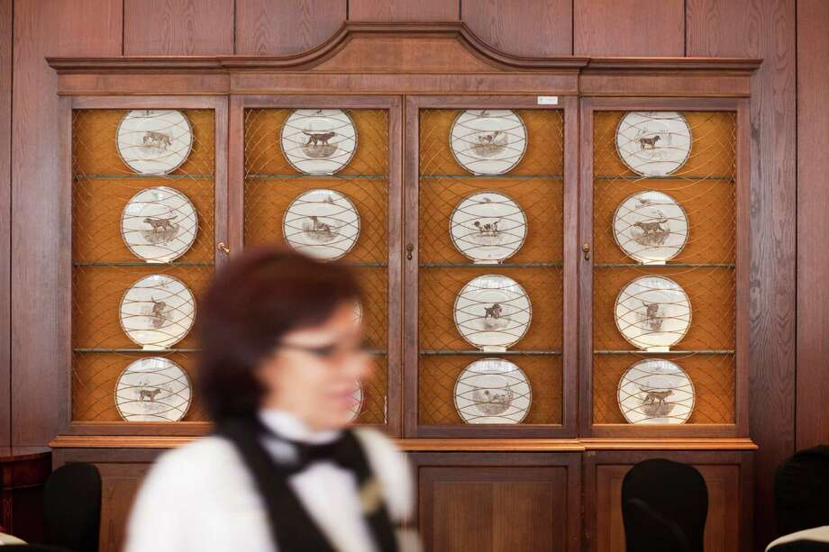 Wedgwood plates of hunting dogs are displayed in a case in the club's dining room. In the recent past, former President George H.W. Bush, Robert Mosbacher and James A. Baker dined in the back corner of the room. Photo: Eric Kayne / © 2012 Eric Kayne