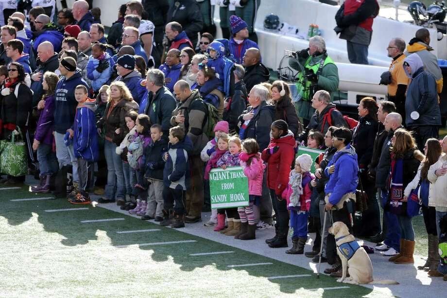 A contingent of teachers, parents, and students from Sandy Hook Elementary School in Newtown, Conn., take part in ceremonies before Sunday's game between the New York Giants and the Philadelphia Eagles at MetLife Stadium, Sunday, Dec. 30, 2012, in East Rutherford, N.J. The school was the site of a mass shooting on Dec. 14. (AP Photo/Peter Morgan) Photo: Peter Morgan