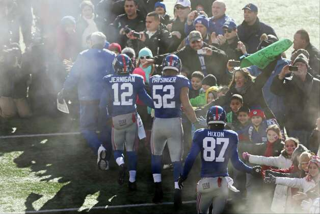 New York Giants wide receiver Jerrel Jernigan (12), Spencer Paysinger (52) and Domenik Hixon (87) greet a contingent of teachers, parents, and students from Sandy Hook Elementary School in Newtown, Conn., before an NFL football game Sunday, Dec. 30, 2012, in East Rutherford, N.J. The school was the site of a mass shooting on Dec. 14. (AP Photo/Peter Morgan) Photo: Peter Morgan