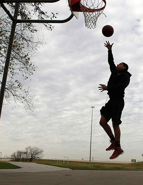 Edwin Escobedo, 15, puts up a lay-up while playing basketball at Herman Brown Park in northeast Houston on Sunday. Escobedo complained that the ball hurt his hands because of the cold weather. Were Escobedo to venture to the courts on Monday, he might find the ball a bit slippery - rainstorms are likely for much of the morning in the Houston area. Photo: Johnny Hanson, Staff / © 2012  Houston Chronicle