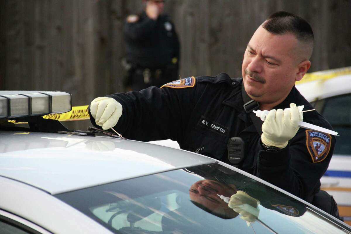 A member of the Harris County Sheriff's Office takes a sample of blood from handcuffs two deputies tried to use while restraining a man in December 2012. The man, Kemal Yazar, was fatally shot by a deputy responding to a call at a Katy home.