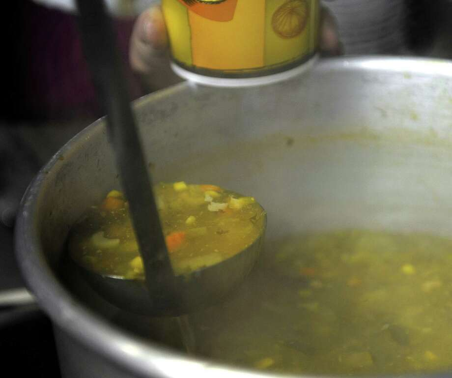 "Chicken vegetable soup is scooped out at the Holy Name of Jesus National Catholic Church during their first Soup on Sunday event on Sunday, Dec. 30, 2012 in Schenectady, NY.  The church's Decon Jim Konicki said that ""the congregation wanted to offer a place for anyone to come for free nourishment, a safe place where people can gather for fellowship and support for one another"".  The church will hold the free Soup on Sunday event the last Sunday of every month from 11:30 am to 1:30 pm.  The Golub Corporation and Hannaford both gave donations that aid in the running of the program.  Decon Konicki said that for the congregation charity and outreach are very important.  (Paul Buckowski / Times Union) Photo: Paul Buckowski  / 00020604A"