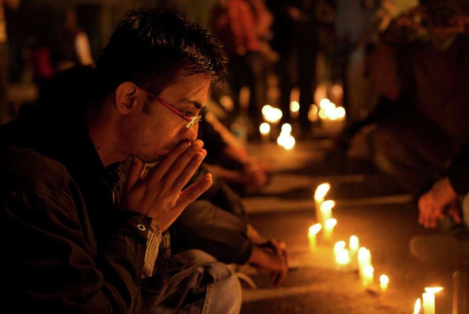 An Indian participates in a candle-lit vigil to mourn the death of a gang rape victim in New Delhi, India, Saturday, Dec. 29, 2012. Indian police charged six men with murder on Saturday, adding to accusations that they beat and gang-raped the woman on a New Delhi bus nearly two weeks ago in a case that shocked the country. The murder charges were laid after the woman died earlier Saturday in a Singapore hospital where she has been flown for treatment. (AP Photo/ Dar Yasin) Photo: Dar Yasin, STR / AP