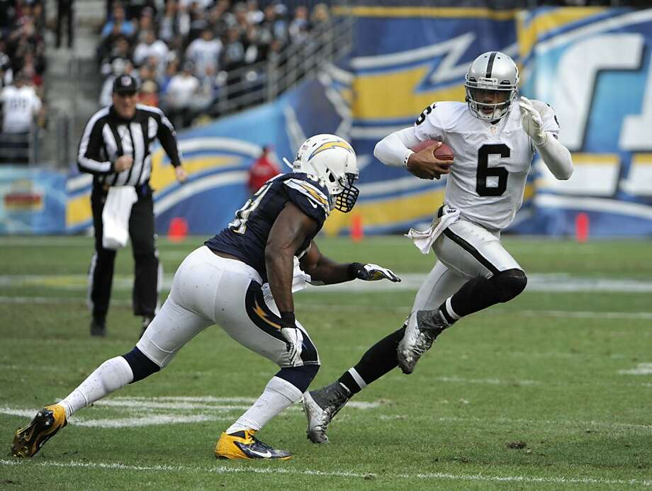 Terrelle Pryor (right, evading Takeo Spikes) had a strong game in the Raiders' season finale at San Diego. Photo: Denis Poroy, Associated Press