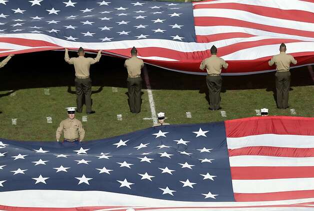 U.S. Marines hold flags on the field before the San Diego Chargers play the Oakland Raiders in an NFL football game Sunday, Dec. 30, 2012, in San Diego. (AP Photo/Gregory Bull) Photo: Gregory Bull, Associated Press