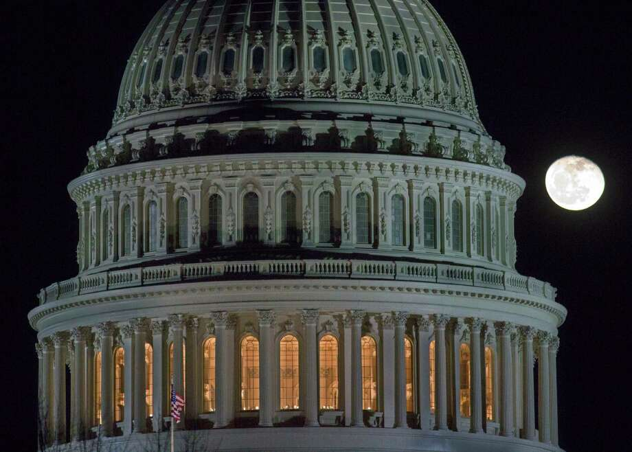 The moon rose behind the Capitol on Sunday as Congress tried unsuccessfully to resolve its stalemate. Photo: J. David Ake, STF / AP