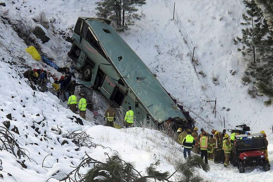 Emergency personnel respond to the scene of a multiple-fatality accident after a tour bus careened through a guardrail along an icy highway and fell several hundred feet down a steep embankment, authorities said, Sunday, Dec. 30, 2012 about 15 miles east of Pendleton, Ore. The charter bus carrying about 40 people lost control around 10:30 a.m. on the snow- and ice-covered lanes of Interstate 84, according to the Oregon State Police. (AP Photo/East Oregonian, Tim Trainor) Photo: Tim Trainor, Associated Press