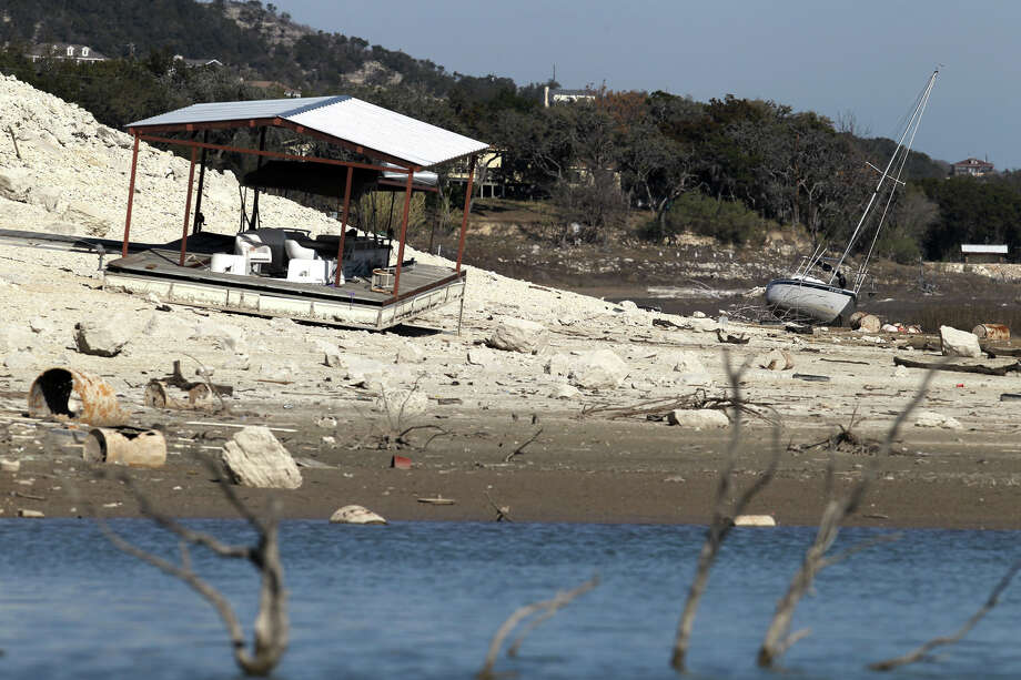 In this Jan. 19, 2012 photo, a sailboat lists on its side on the ground next to a beached dock as water levels at Medina Lake, Texas continued to drop. Photo: JOHN DAVENPORT / San Antonio Express-News