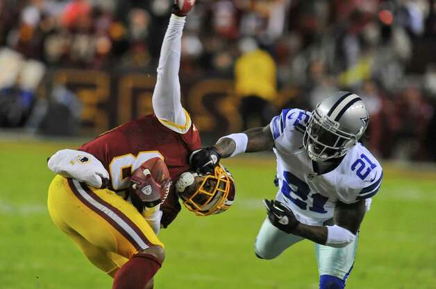 Washington Redskins wide receiver Santana Moss (89) is tackled by Dallas Cowboys cornerback Mike Jenkins (21) during the first half of an NFL football game Sunday, Dec. 30, 2012, in Landover, Md. (AP Photo/Richard Lipski) Photo: Richard Lipski, Associated Press / FR170623 AP